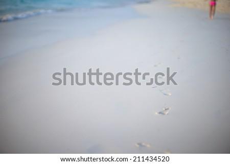 Human footprints on white sand beach - stock photo