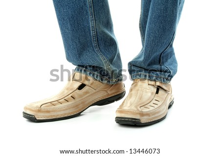 Human foots with brown leather shoes and jeans, isolated on white
