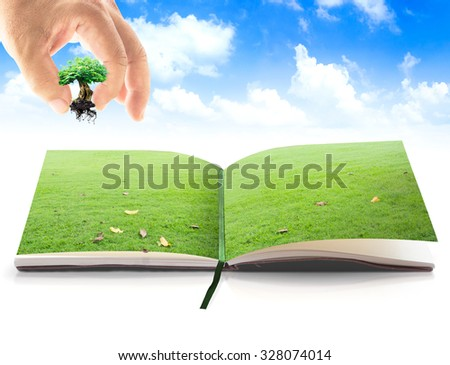 Human hand add growing tree or big plant into opening book in meadow over beautiful blue sky background. Natural Energy Ecology Investment CSR Food Soil Idea God Lesson One Save Bank Gift Seed concept - stock photo