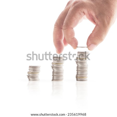Human hand adding a coin in the third row on white background. Money coin concept.