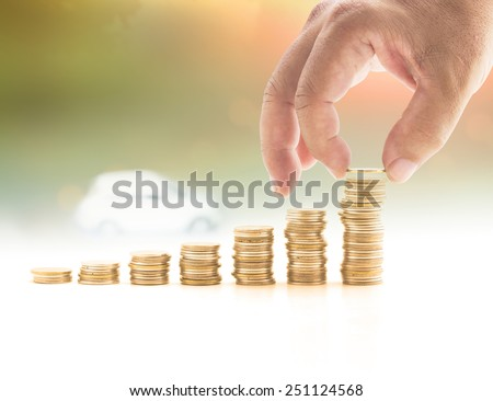 Human hand adding a golden coin in the final row of golden coins over blurred white car on sunset background. Concept for money coin, insurance, buying, renting, repair, fuel , service. - stock photo