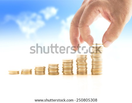 Human hand adding a golden coin in the final row over blurred world map of clouds background. Money coin concept. - stock photo