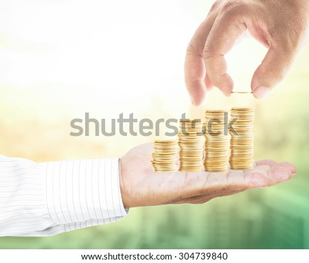 Human hand adding a golden coin over blurred city background. Money coin, insurance, buying, rent, international monetary fund, anti corruption day, IMF, banking, assurance, CSR concept. - stock photo