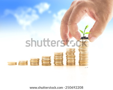 Human hand adding a golden coin with young plant in the final row over blurred world map of clouds background. Money coin concept. - stock photo
