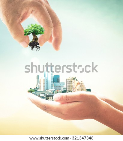Human hand adding big plant into the city in another hands on beautiful blurred sunset background. Ecological City, Ecology, World Environment Day, Creation from bible, Investment, ROI, LIT concept.  - stock photo