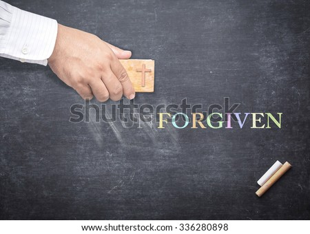 Human hand erased alphabet U, N from a chalkboard for changing to FORGIVEN. The word UNFORGIVEN erased from a chalkboard. Concept of Forgiven, Mercy, Repentance, Reconcile, Change. - stock photo
