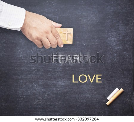 Human hand erased the word FEAR from a chalkboard for changing to LOVE. Change concept. Concept of Jesus erasing sin. - stock photo