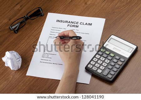 Human hand filling out an empty insurance form on a desk with eye glasses and calculator - stock photo