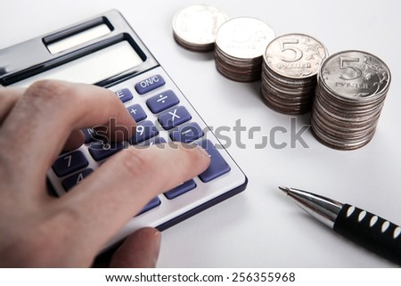 human hand for a calculator and money close up - stock photo