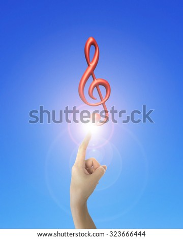 Human hand forefinger pointing at 3D music note with bright light, on blue background. - stock photo