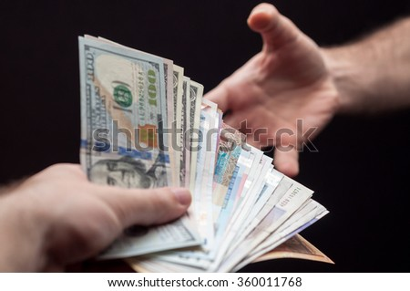 Human hand grabbing fan of banknotes from various counties on dark background - stock photo