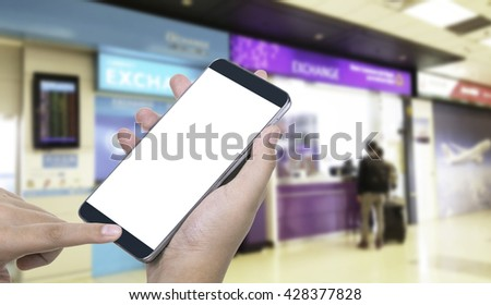 Human hand hold and touch screen smart phone, tablet,cellphone on blurred in airport background; With clipping path on screen Smart Phone. blank screen for your advertising. - stock photo