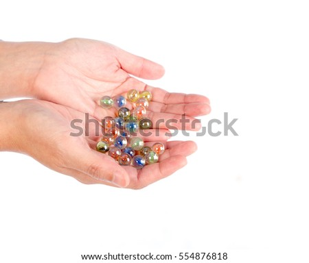 Human hand hold glass marbles balls on white blackground, selective focus
