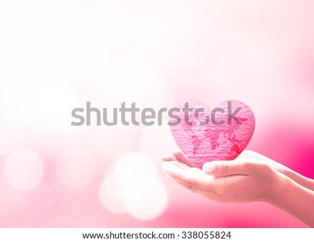 Human hand hold world map with red heart made of fabric texture on blur abstract beautiful pink bokeh colorful sunset background. Medicine Cancer Ovarian World Blood Donor Day concept - stock photo