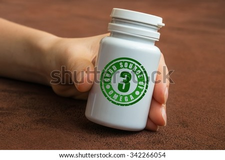 Human hand holding a bottle of pills with Omega-3 on brown background - stock photo
