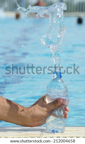 Human hand holding a bottle of water  - stock photo