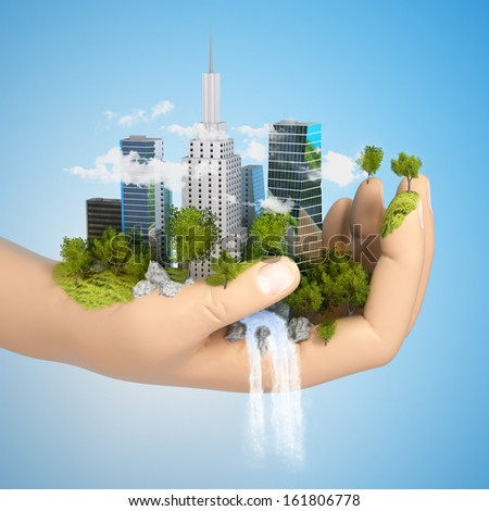 human hand holding a city on green grass hill with river, 3d - stock photo