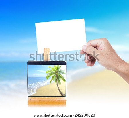 Human hand holding a empty paper and picture of the beach on paper clip over the actual location. World environment day, Ocean. - stock photo