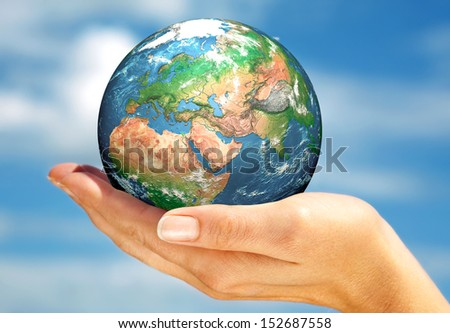 Human hand holding a globe. Elements of this image furnished by NASA. - stock photo