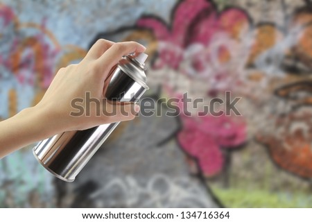 Human hand holding a graffiti Spray can in front of a colorful wall - stock photo