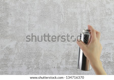 Human hand holding a graffiti Spray can in front of blank concrete wall - stock photo