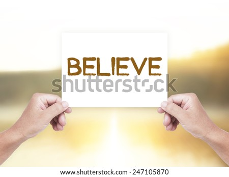 Human hand holding a handwritten text for BELIEVE over blurred nature background. - stock photo