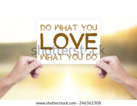 Human hand holding a handwritten text for DO WHAT YOU LOVE WHAT YOU DO over blurred nature background. - stock photo