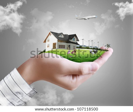 human hand holding a house ands nature - stock photo