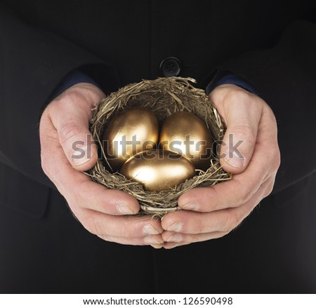 Human hand holding a nest with three golden eggs inside - stock photo