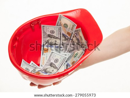 Human hand holding a red hard hat with money, white background