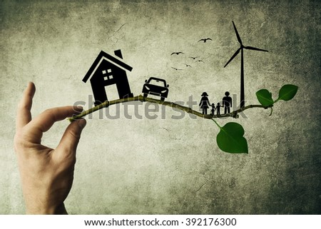 Human hand holding a tree branch. Environmental green energy concept. Silhouette of happy family, house, car and windmill - stock photo