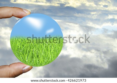 human hand holding abstract sphere with green grass and blue sky on the cloudy background