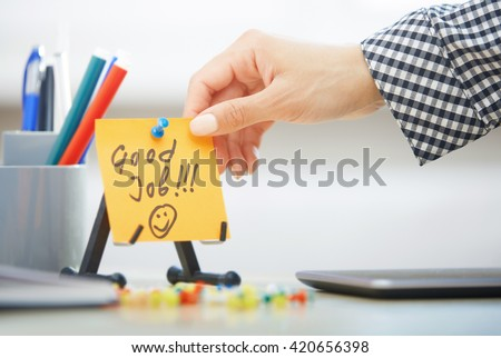 Human hand holding adhesive note with Good Job text
