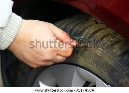 human hand holding an rusty nail piercing the tire wheel