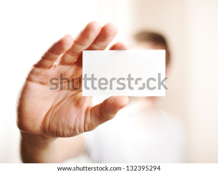 Human hand holding blank business card with copy space, small dof - stock photo