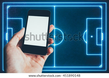 Human Hand Holding Blank Screen Smartphone with Top view of soccer field or football field  - stock photo