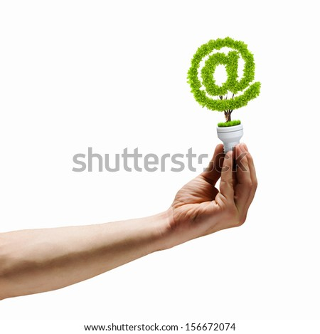 Human hand holding bulb with plant shaped like at symbol