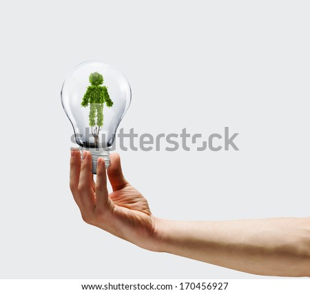 Human hand holding bulb with plant shaped like man