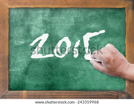 Human hand holding chalk and writing text for 2015 on green board. - stock photo