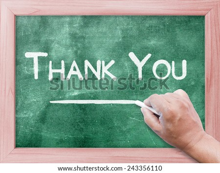 Human hand holding chalk and writing text for THANK YOU on green board. - stock photo