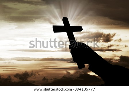 Human hand holding christian cross with sky background