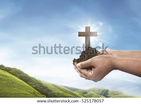 Human hand holding christian cross with soil on the hand over blue sky background