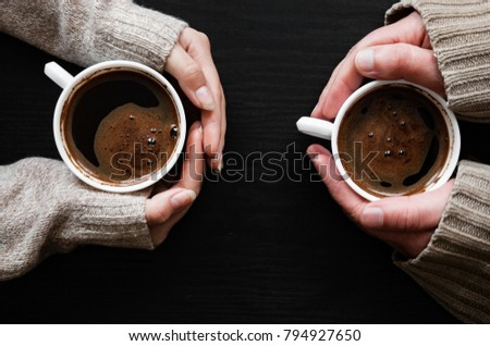 Human Hand Holding Coffee Cup on dark wooden background