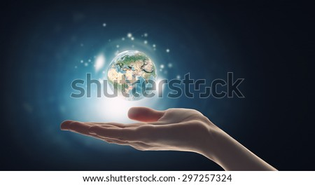 Human hand holding digital icon of planet earth. Elements of this image are furnished by NASA