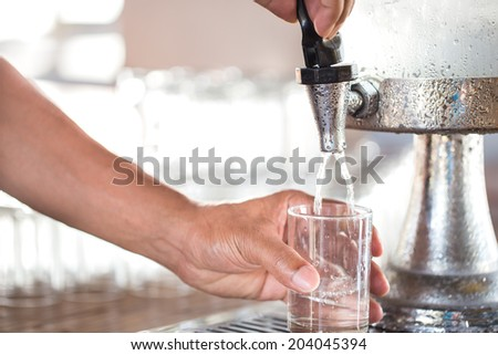 Human hand holding glass pouring fresh drink water - stock photo