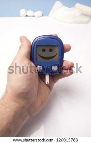 Human Hand Holding Glucometer shoving smiley face. Conceptual image - stock photo
