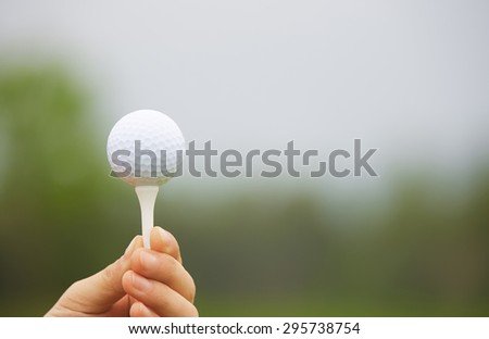 Human hand holding golf ball on a support - stock photo