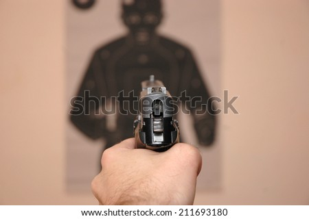 Human hand holding gun and aim at a target - stock photo