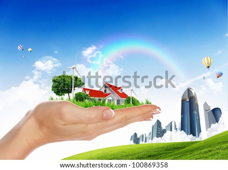 Human hand holding houses surrounded by nature against blue sky and rainbow - stock photo