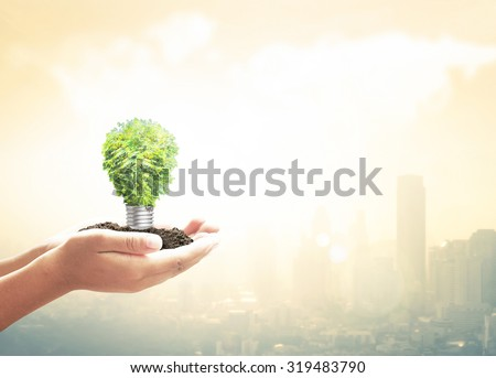 Human hand holding light bulb of tree on blurred beautiful golden warm sunrise city over world map of clouds background. World Soil Day concept. - stock photo